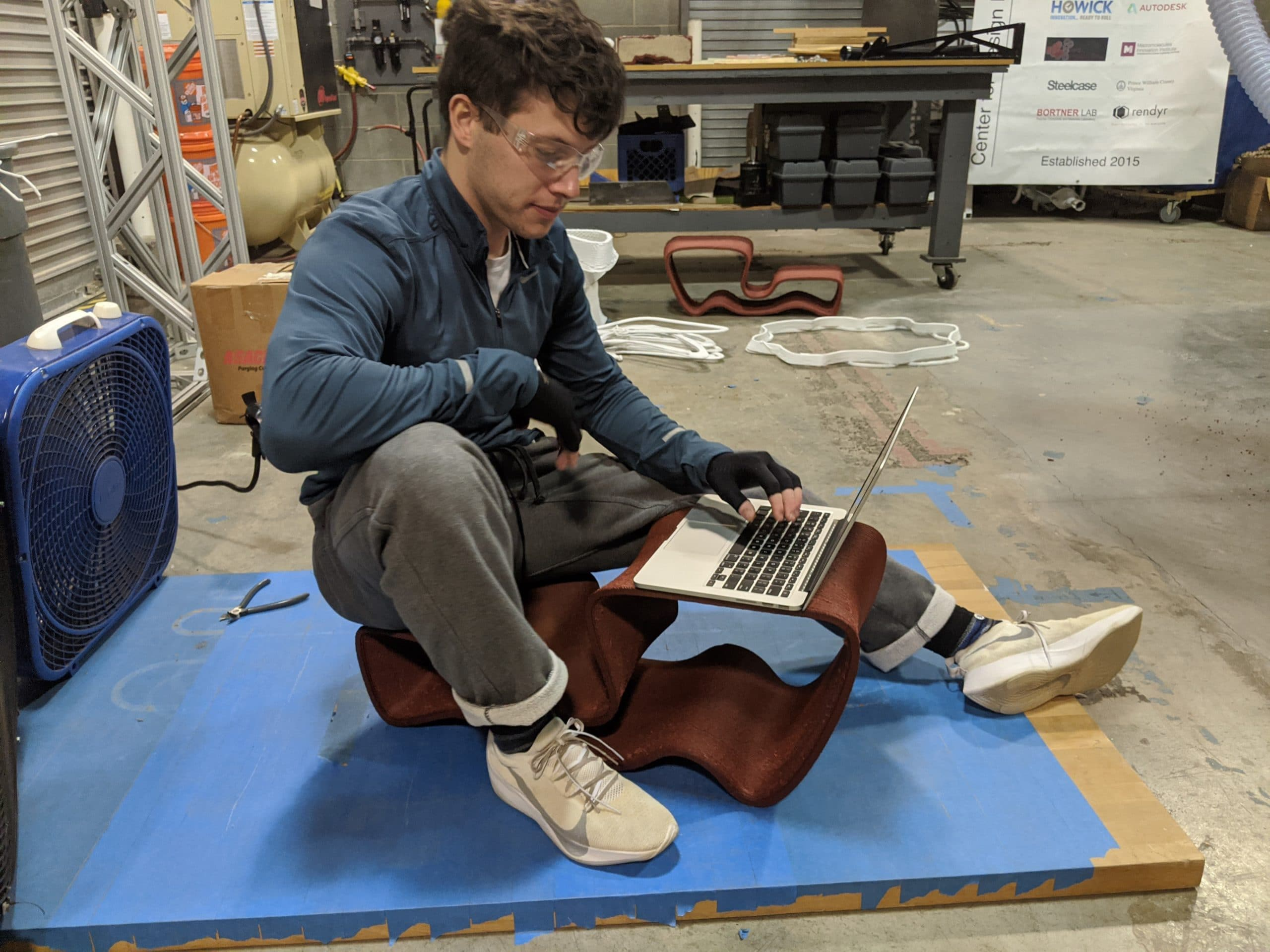 Man sitting & working on his laptop on a 3D printed outdoor chair designed in Gravity Sketch